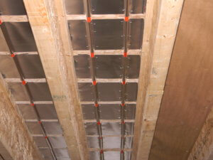 Photo showing the aluminum heat transfer plates installed in continuous coverage for a radiant floor heating system.